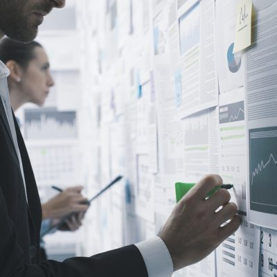 Business people analyzing financial charts and reports on a wall, strategies and analytics concept